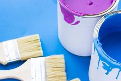 House renovation concept, paint cans and brushes. House renovation, paint cans and paintbrushes on blue background stock photography