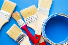 House renovation concept, paint cans and brushes. House renovation, paint cans and paintbrushes on blue background top view royalty free stock photography
