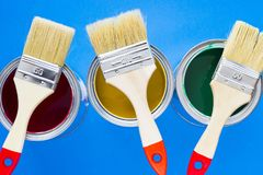 House renovation concept, paint cans and brushes. House renovation, paint cans and paintbrushes on blue background top view stock photos