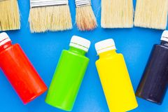 House renovation concept, paint cans and brushes. House renovation, paint cans and paintbrushes on blue background top view stock images