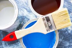 House renovation concept, paint cans and brushes. House renovation, paint cans and paintbrushes on blue mystic background stock photography