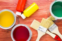 House renovation concept, paint cans and brushes. House renovation, paint cans and paintbrushes on the old wooden background top view stock photos