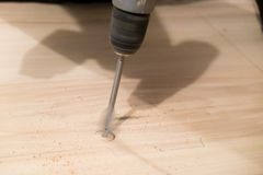 House Renovation and Remodel. Drilling into a wood countertop with an inch drill bit during a house remodel Stock Photo