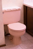 House Renovation and Remodel. Outdated pink toilette at a house remodel and renovation Stock Image