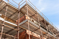 House for renovation with the scaffolding for bricklayers. Construction scaffolding of a building under renovation Stock Photos