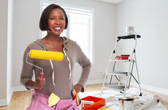 House renovation. Smiling african-american woman doing painting and renovation Stock Images