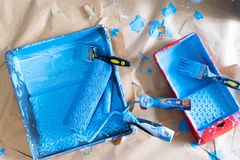 House renovation tools. In blue paint stains on brown craft paper stock image