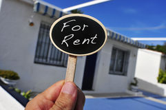 House for rent. A man hand holding a signboard with the text for rent written in it in front of a house Royalty Free Stock Image