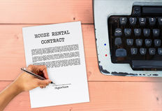 House rental agreement with hand signing. On signature paper, with typewriter on wood table, vintage contract sign Stock Photo