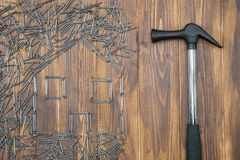 House repair, house shape by Group of nail with hammer Royalty Free Stock Photos