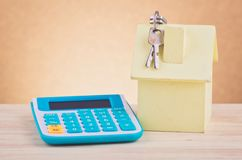 House replica and calculator on wooden desk for home loan and financing. Concept royalty free stock photo