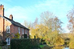 house resting by river in English countryside Royalty Free Stock Photo