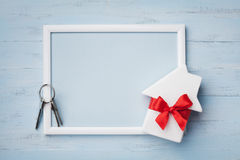 House with ribbon, frame and keychain on wooden background. Buying a new home, planning housewarming, gift or sale of real estate. Miniature white house royalty free stock image