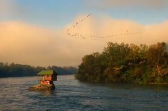 House in river Drina near Bajina Basta and flock of flying birds, Western Serbia Royalty Free Stock Photography
