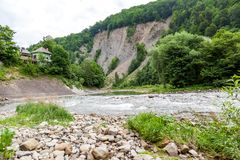 House on the river near mountain Stock Photography