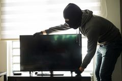 House robber taking a tv with him. House robber wearing a ski mask and stealing some stuff in the middle of the day Stock Photos