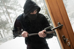 House robbery - robber trying open door with crowbar. House robbery - robber with face mask trying open door with crowbar Stock Photos