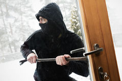 House robbery - robber trying open door with crowbar. House robbery - robber with face mask trying open door with crowbar Royalty Free Stock Photos