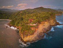 House on rock cliff. In ocean bay aerial view sunset time Royalty Free Stock Photography