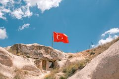 Turkey flag. House in rock with the flag of Turkey against blue sky with cumulus clouds. House in rock with the flag of Turkey against blue sky with cumulus stock photo