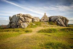 House between the rocks in Meneham village, Kerlouan, Finistere, Brittany Bretagne, France. The village of Meneham, located in Pagan county Pagan bro, was Stock Image