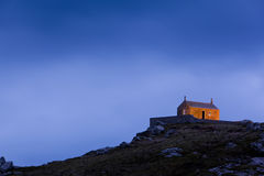 House on Rocky Hill at Night. Old stone building on top of a rocky hill at night Royalty Free Stock Image