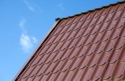 House roof from brown metal tile closeup Stock Images