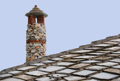 House roof and chimney made of stones. Detail of a house roof and a chimney made of stones Stock Images