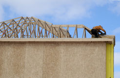 House / Roof Construction. Worker on the roof of residential house being built royalty free stock photos