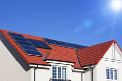 House roof covered with solar panels. Alternative energy photovoltaic solar panels on tiled house roof Royalty Free Stock Image