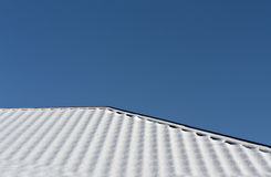 House roof in snow against blue sky. Stock Photos