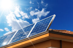 House Roof with Solar Panels. Close-up of a house roof with a solar panels on top, on a blue sky with clouds and sun rays stock photography