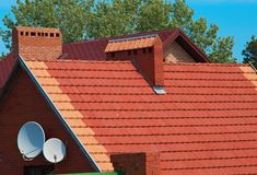 House roof with TV dish and pipes Royalty Free Stock Image