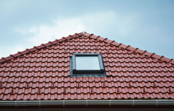 House roof window, sun tunnel skylights or skylight after rain on red clay  roof tiles. Attic skylight solution outdoor. Roofing. Royalty Free Stock Image