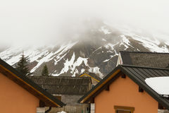 House Roofs Side Snow Mountain. Rooftops of a village on the side of a snowy mountain and fog Low clouds Stock Images