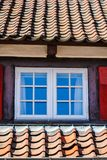 Window in an old building. House between the roofs in an small town Royalty Free Stock Photos