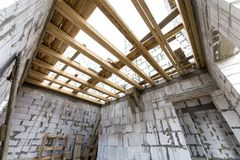 House room interior under construction and renovation. Energy saving walls of hollow foam insulation blocks, wooden ceiling beams. And roof frame royalty free stock images