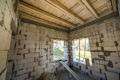 House room interior under construction and renovation. Energy saving walls of hollow foam insulation blocks, wooden ceiling beams. And roof frame royalty free stock photo