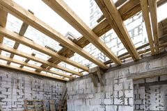 House room interior under construction and renovation. Energy saving walls of hollow foam insulation blocks, wooden ceiling beams. And roof frame royalty free stock image