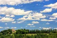 House with row of cypress trees on top of the hill in Val d`Orci Stock Photography