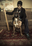 House safety. Man with his baseball bat and a bulldog sitting at home Stock Photography