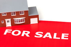 House For Sale. House sitting on a large red for sale sign Royalty Free Stock Image