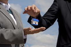 House for sale. Hand giving a house key holder  on a blue sky background Royalty Free Stock Image