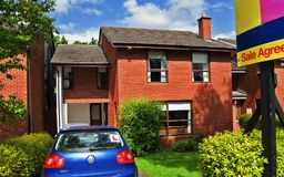 House for Sale. On a sunny day signposted with blue car in driveway Stock Images