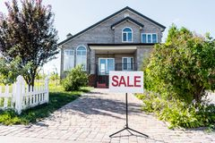House for sale. Beautiful house with sign sale standing on pathway stock images
