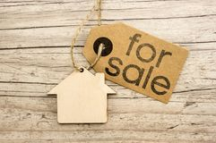 House for sale. Peper tag on wooden house cutout close up writing for sale stock photography