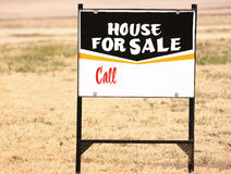 House For Sale Sign. A simple real estate sign standing in the dry grass. Sign says House For Sale - Call Stock Photography