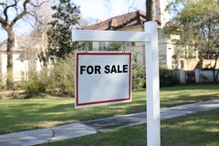 House for sale. A for sale sign hanging in front of a house royalty free stock images