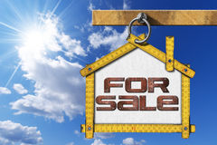 House For Sale Sign - Wooden Meter. Yellow wooden meter ruler in the shape of house with text for sale. For sale real estate sign on blue sky with cloud and sun royalty free illustration