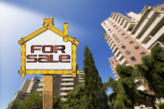 House For Sale Sign - Wooden Meter. Yellow wooden meter ruler in the shape of house with text for sale. For sale real estate sign with tall and blurred buildings stock illustration